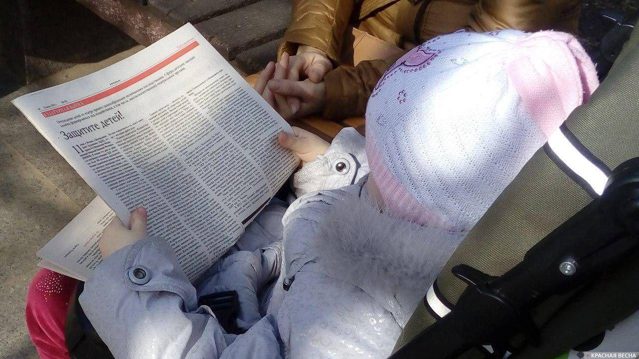 Надпись на газете «Защитите детей!» Игорь Кудряшов © ИА Красная Весна